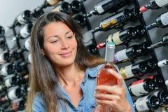 Jeune femme choisissant le vin de bouteille Photos libres de droits
