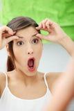 Jeune femme choqué contrôlant ses rides Image libre de droits