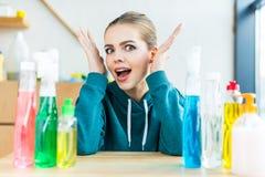 jeune femme choquée regardant l'appareil-photo tout en se reposant à la table avec les bouteilles en plastique image libre de droits