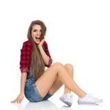 Jeune femme choquée s'asseyant sur un plancher Photographie stock libre de droits