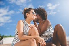 Jeune femme chuchotant à son ami dehors Photos libres de droits