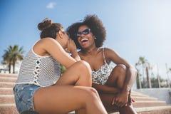 Jeune femme chuchotant à son ami riant Photos libres de droits