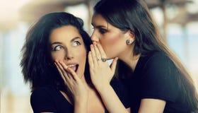 Jeune femme chuchotant un secret à un ami féminin Rumeurs Conce photos libres de droits