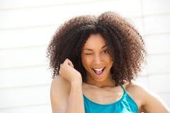 Jeune femme clignant de l'oeil le sourire d'oeil Image libre de droits