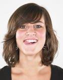 Jeune femme collant la langue à l'extérieur Images stock