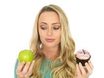 Jeune femme comparant la bonne et gâtée nourriture Photo libre de droits