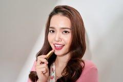 Jeune femme composant avec un rouge à lèvres photo stock
