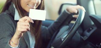 Jeune femme conduisant et tenant la carte de visite professionnelle de visite images libres de droits
