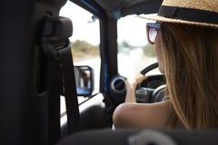 Jeune femme conduisant la voiture à couvercle serti sur la route de campagne Image libre de droits
