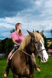 Jeune femme conduisant les chevaux sur le pré Photographie stock libre de droits
