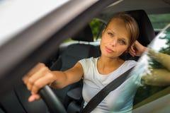 Jeune femme conduisant son véhicule photo stock