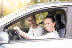 Jeune femme conduisant, un homme presque s'asseyant dans la voiture Photo libre de droits