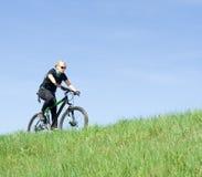 Jeune femme conduisant un vélo de montagne Photographie stock libre de droits