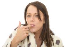 Jeune femme confortable décontractée heureuse attirante suçant son doigt images libres de droits