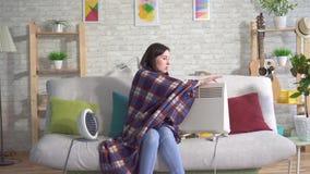 Jeune femme congelée dans le salon et se dorer à côté des radiateurs électriques banque de vidéos