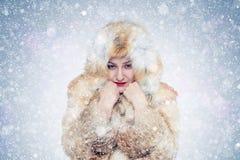 Jeune femme congelée dans un manteau de fourrure de renard, froid, neige, gel, tempête de neige photo libre de droits