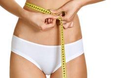 Jeune femme conscient mesurant sa taille Photos libres de droits