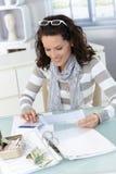 Jeune femme contrôlant des factures Image stock