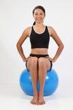 Jeune femme convenable équilibrant sur la bille bleue d'exercice Image stock