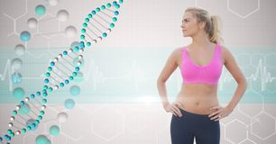 Jeune femme convenable avec des mains sur des hanches regardant la structure d'ADN Images stock