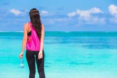 Jeune femme convenable avec la bouteille de l'eau sur tropical Photos stock