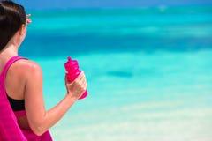 Jeune femme convenable avec la bouteille sur le blanc tropical Images libres de droits