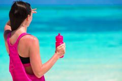 Jeune femme convenable avec la bouteille sur le blanc tropical Photographie stock libre de droits