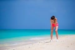 Jeune femme convenable courant sur la plage tropicale dans ses vêtements de sport Image stock