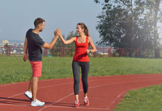 Jeune femme convenable donnant la haute cinq à son ami après une course Photographie stock