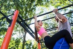Jeune femme convenable faisant traction-UPS soutenu par son associé fort Image stock