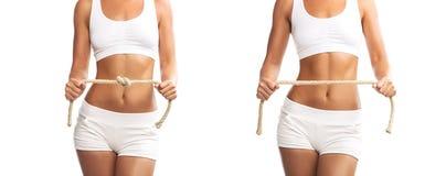 Jeune femme convenable tenant une corde attachée et déliée au-dessus de son abdomen, sur le fond blanc Image libre de droits