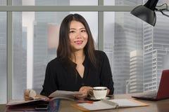 Jeune femme coréenne asiatique heureuse et belle d'entrepreneur travaillant au bureau moderne d'ordinateur de bureau au district  photographie stock