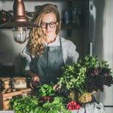 Jeune femme coupant des herbes et des légumes dans la cuisine, culture carrée photographie stock