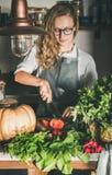 Jeune femme coupant les herbes et les légumes frais pour la cuisson photographie stock
