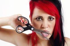 Jeune femme coupant sa langue avec des ciseaux Images stock