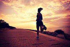 Jeune femme courant au bord de la mer de lever de soleil Photographie stock