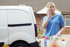 Jeune femme courant des affaires mobiles de nettoyage avec Van Using Mobi Photo libre de droits