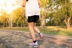 Jeune femme courant en bois, formation et s'exerçant pour la résistance de marathon de course de traînée dans le lever de soleil  Photographie stock libre de droits
