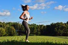 Jeune femme courant en parc pendant la formation de sport photographie stock libre de droits