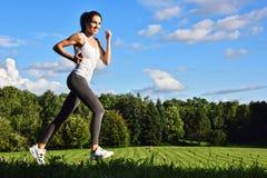 Jeune femme courant en parc pendant la formation de sport photo stock