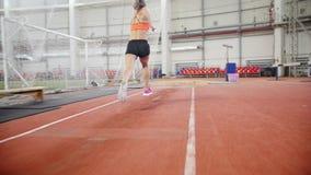 Jeune femme courant et exécutant un long saut dans l'arène de sports banque de vidéos