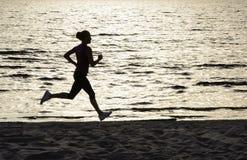 Jeune femme courant le long du rivage de lac Image stock