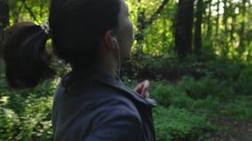 Jeune femme courant par la forêt sur le coucher du soleil Pulser sur la nature banque de vidéos