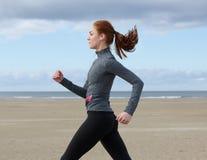 Jeune femme courant par la plage Image stock
