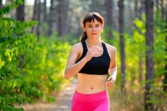 Jeune femme courant sur la traînée dans beau Forest Active Lifestyle Concept sauvage L'espace pour le texte photographie stock libre de droits