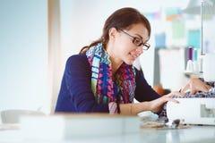 Jeune femme cousant tout en se reposant à son lieu de travail Photo libre de droits