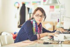 Jeune femme cousant tout en se reposant à son lieu de travail Photographie stock libre de droits