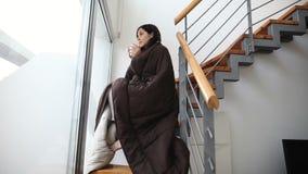 Jeune femme couverte de couverture buvant du café chaud banque de vidéos