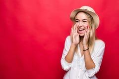 Jeune femme criarde dans la position de chapeau de paille d'isolement au-dessus du fond rouge image stock