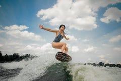 Jeune femme criarde sautant sur le conseil wakesurfing sur le ri photos stock